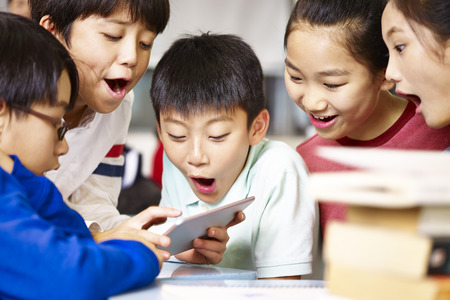 Photo for group of asian elementary school children gathering around playing game together using tablet during break. - Royalty Free Image