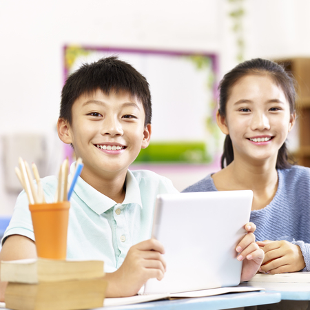 Photo for portrait of two happy asian primary school students looking at camera smiling. - Royalty Free Image