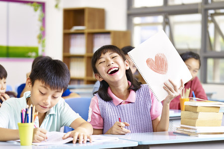 Foto de happy and lovely asian elementary school girl showing a drawing and laughing. - Imagen libre de derechos