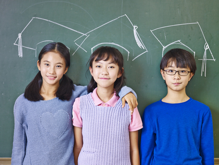 Photo pour three asian elementary school children standing in front of chalkboard underneath chalk-drawn doctoral caps. - image libre de droit