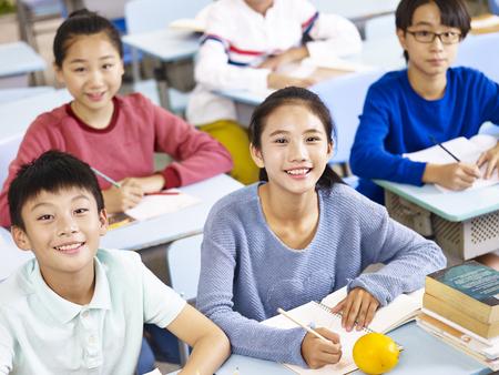 Foto de asian grade school students sitting in classroom, high angle view. - Imagen libre de derechos