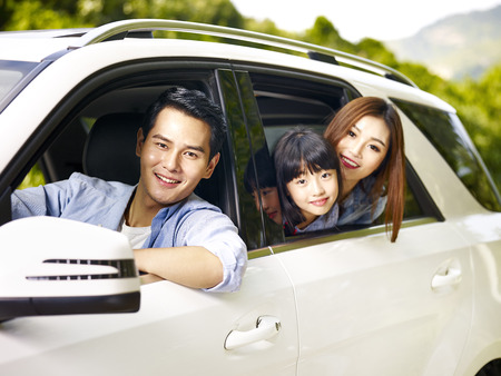 Photo pour happy asian family traveling by car looking at camera smiling. - image libre de droit