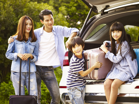 Photo pour cute asian children helping unloading luggage from trunk while parents watching affectionately. - image libre de droit