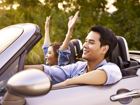 Photo pour young asian couple riding in a convertible sport car at sunset. - image libre de droit