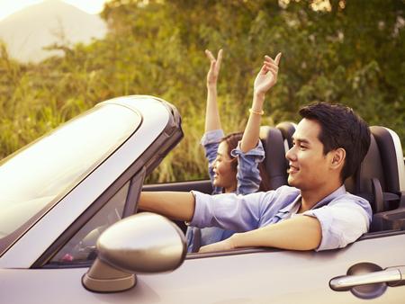 Photo pour young asian couple riding in a convertible sport car enjoying the cool breeze at sunset. - image libre de droit