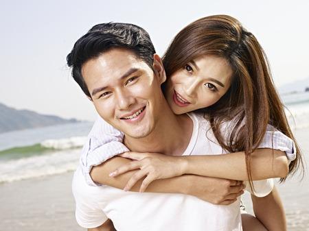 Foto de young asian man carrying girlfriend or wife on back on beach. - Imagen libre de derechos