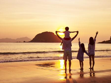 Photo pour asian family standing on beach watching and enjoying the sunrise or sunset. - image libre de droit