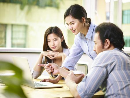 Foto de a team of young asian corporate executives discussing business in office using laptop computer. - Imagen libre de derechos