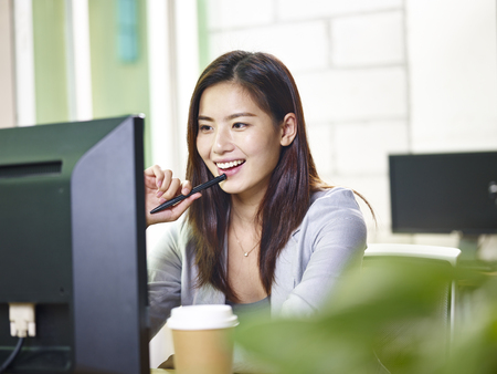 Photo pour young asian businesswoman working in office using computer. - image libre de droit