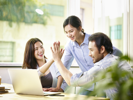 Foto de young asian business person giving coworker high five in office celebrating achievement and success. - Imagen libre de derechos