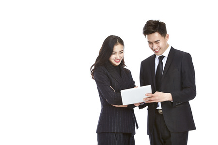 Foto de young asian businessman and businesswoman working together using mini digital tablet, isolated on white background. - Imagen libre de derechos
