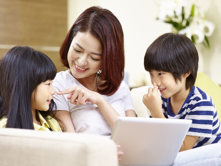 Photo pour young asian mother sitting on couch at home having fun playing with son and daughter. - image libre de droit
