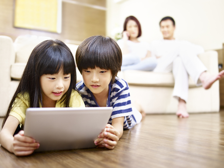 Photo pour two asian children lying on floor playing video game using digital tablet while parents watching in the background. - image libre de droit