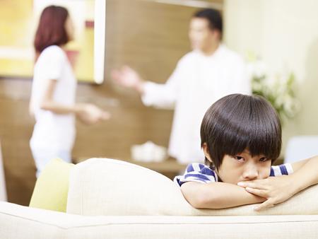 Foto de asian child appears sad and unhappy while parents quarreling in the background. - Imagen libre de derechos