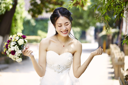 Photo pour young and beautiful asian bride rejoicing with bouquet in hand. - image libre de droit