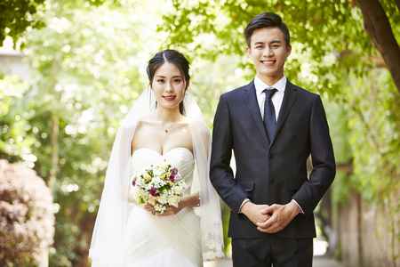 Foto de outdoor portrait of asian bride and groom looking at camera smiling. - Imagen libre de derechos