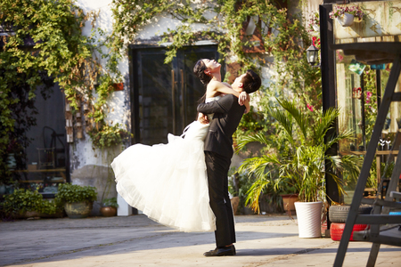 Photo for asian newly wed bride and groom celebrating marriage outside a building. - Royalty Free Image
