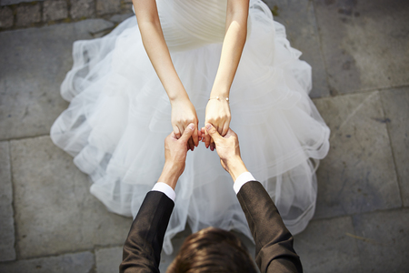 Foto de young asian bride and groom holding hands and dancing, high angle view. - Imagen libre de derechos