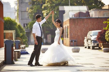 Foto de young asian bride and groom in wedding dress dancing in parking lot. - Imagen libre de derechos