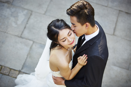 Photo for young asian bride and groom embracing kissing dancing in open air, high angle view. - Royalty Free Image