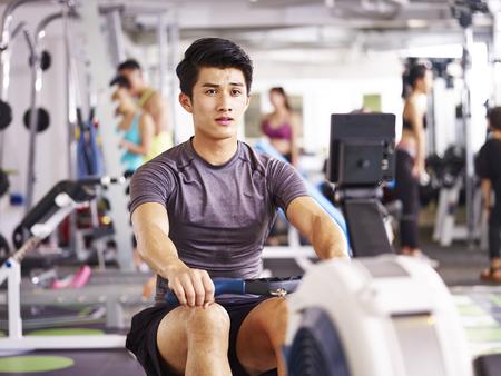 Foto de young asian adult man working out in gym using rowing machine. - Imagen libre de derechos