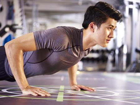 Foto de young asian adult man exercising in gym doing push-ups, side view. - Imagen libre de derechos