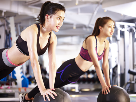 Photo pour two young asian adult women working out in gym using medicine balls. - image libre de droit
