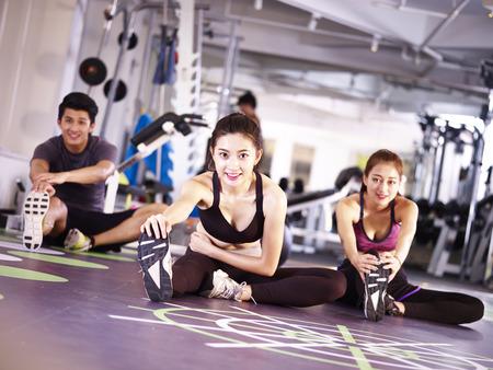 Foto de three young asian adult people exercising in gym stretching legs. - Imagen libre de derechos