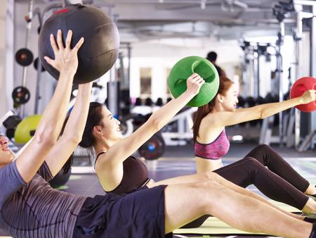 Foto de three young asian adult people working out in fitness center using medicine balls. - Imagen libre de derechos