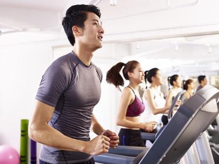 Foto de young asian adult working out on treadmill. - Imagen libre de derechos