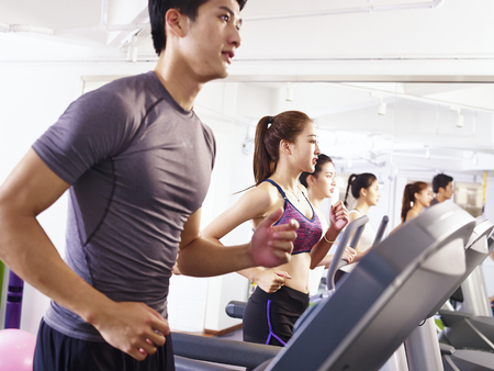 Foto de young asian adult working out on treadmill, focus on the girl in the middle. - Imagen libre de derechos