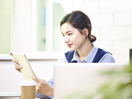 Photo for young asian business woman working in office using laptop computer and digital tablet. - Royalty Free Image