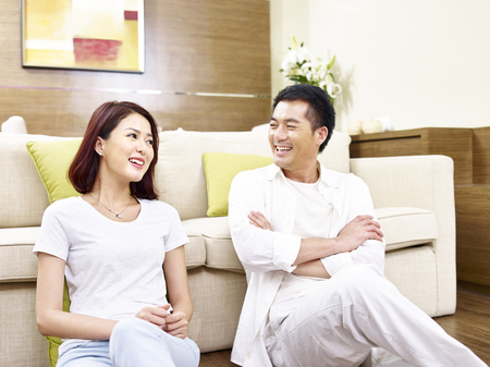 Foto de asian couple sitting relaxing chatting on the floor at home. - Imagen libre de derechos