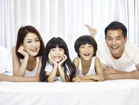 Photo for happy asian family with two children lying on front in bed looking at camera smiling. - Royalty Free Image