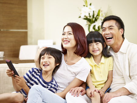 Foto de happy asian family with two children sitting on couch at home watching TV. - Imagen libre de derechos