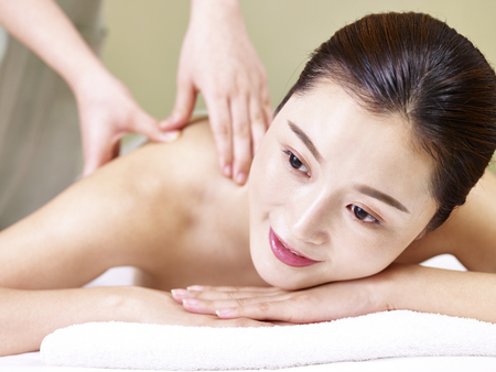 Foto de close-up of face of a beautiful young asian woman lying in front on bed receiving massage in spa salon. - Imagen libre de derechos