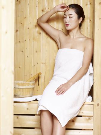 Foto de beautiful young asian woman wrapped in white towel sitting in sauna looking at camera smiling. - Imagen libre de derechos