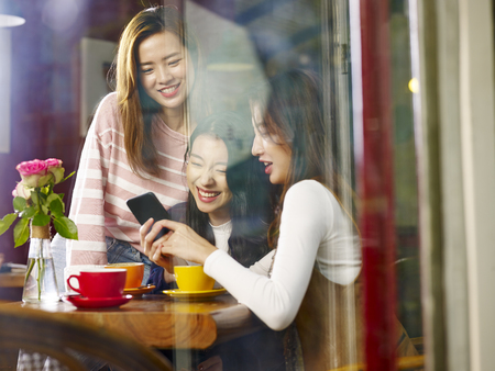 Photo for three beautiful young asian women playing with cellphone in coffee shop or tea house, shot through window glass. - Royalty Free Image