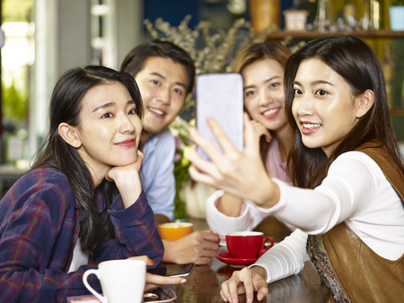 Photo pour group of young asian adults man and women at coffee shop taking a selfie. - image libre de droit