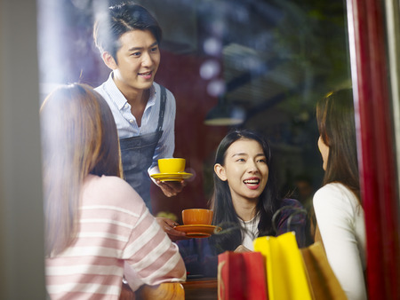 Photo pour young asian waiter serving female customers in coffee shop, shot through window glass. - image libre de droit
