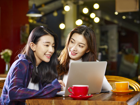 Foto de two happy young asian women sitting in coffee shop looking at laptop computer together. - Imagen libre de derechos