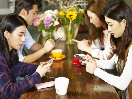 Photo for four young asian adults man and women sitting in coffee shop playing with mobile phone with very serious facial expression. - Royalty Free Image