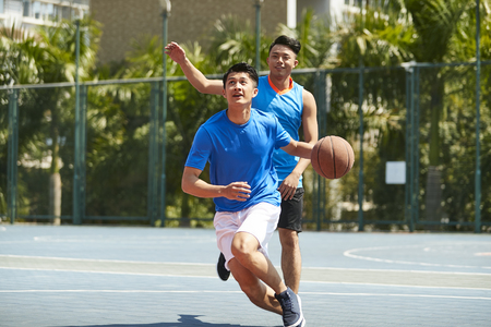 Photo pour young asian male basketball player playing one-on-one on outdoor court. - image libre de droit
