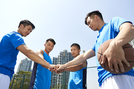 Photo pour young asian basketball players putting fists together to show unity before playing a game. - image libre de droit