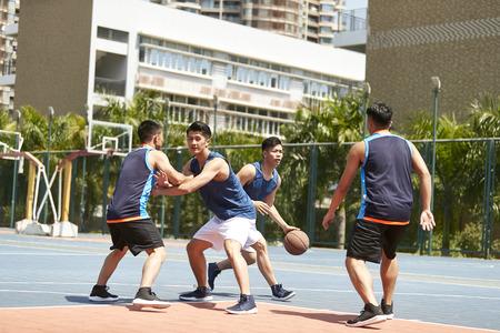 Foto de young asian adult players playing basketball on outdoor court. - Imagen libre de derechos