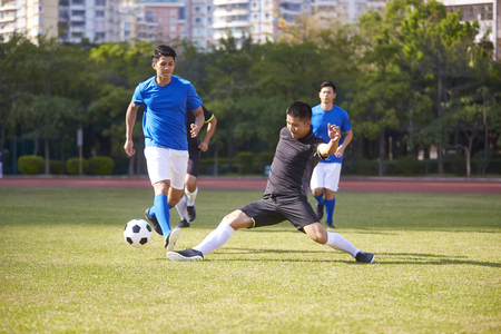 Photo pour a group of young asian soccer football player playing on outdoor court. - image libre de droit
