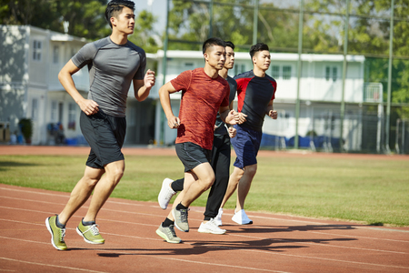 Photo pour four young asian track and field athletes racing competing against each other. - image libre de droit