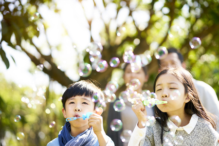 Foto de little asian kids boy and girl sister and brother blowing bubbles in a park with parents watching from behind. - Imagen libre de derechos