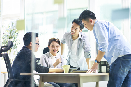 Photo for group of four happy young asian corporate executives working together meeting in office discussing business in office. - Royalty Free Image