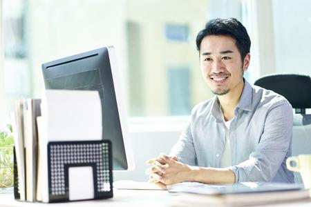 Foto de young asian business man sitting by desk in front of desktop computer looking at camera smiling. - Imagen libre de derechos